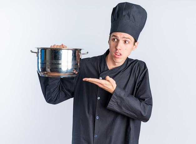 Jeune homme blond ignorant cuisinier en uniforme de chef et casquette tenant et pointant sur le pot regardant le côté isolé sur le mur blanc