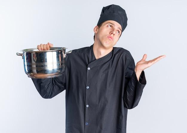 Un jeune homme blond ignorant cuisinier en uniforme de chef et une casquette tenant un pot en levant montrant une main vide isolée sur un mur blanc
