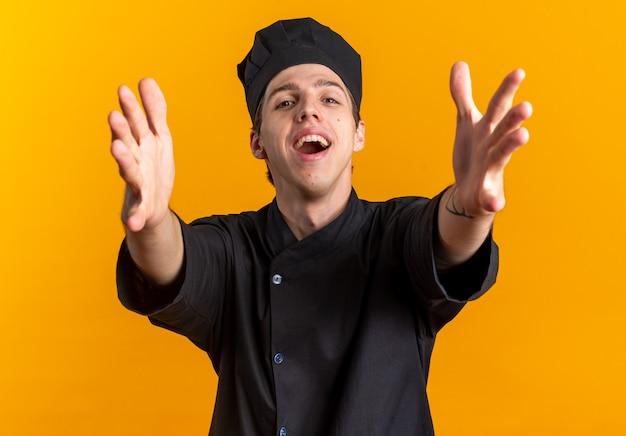 Jeune homme blond joyeux et sympathique cuisinier en uniforme de chef et casquette faisant un geste de bienvenue