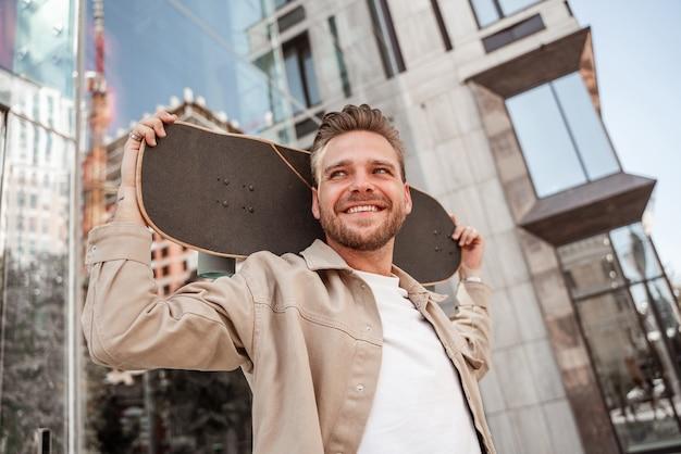 Jeune homme blond joyeux tenant un longboard sur l'épaule dans la rue de la ville. porte une tenue en jean beige. skateur sportif pensant à un nouveau truc extrême à l'extérieur.