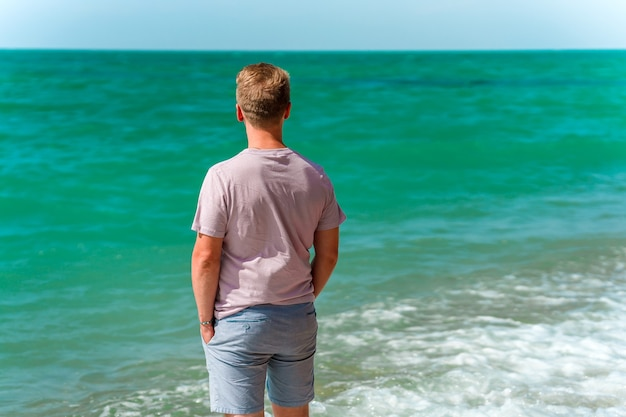 Un jeune homme blond marche sur la plage près de l'océan ou de la mer azur le concept d'un été heureux