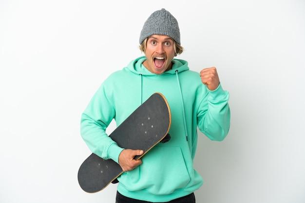 Jeune homme blond patineur isolé célébrant une victoire en position de vainqueur