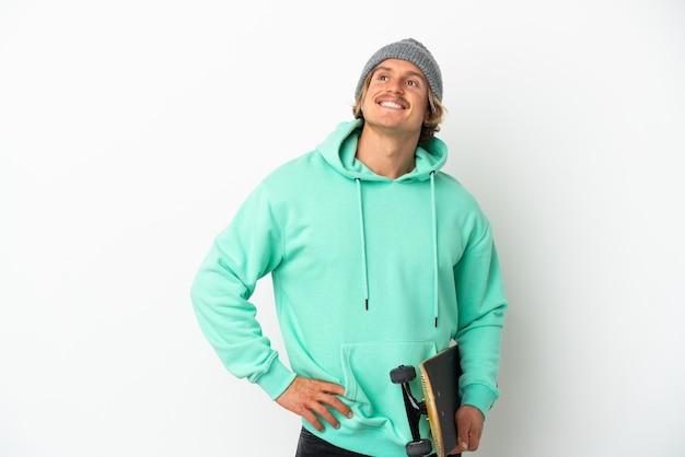 Jeune homme blond patineur isolé sur fond blanc posant avec les bras à la hanche et souriant