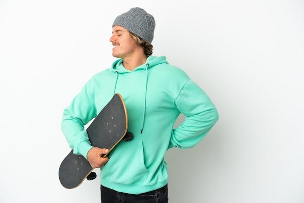 Jeune homme blond patineur isolé souffrant de maux de dos pour avoir fait un effort