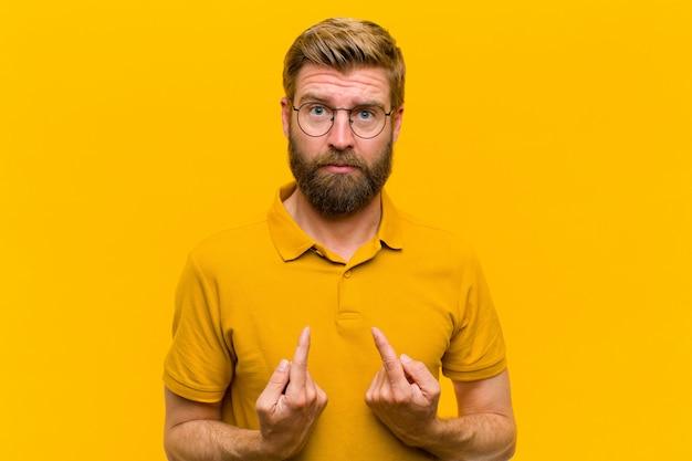 Jeune homme blond pointant sur lui-même avec un regard confus et interrogateur, choqué et surpris d'être choisi sur un mur orange