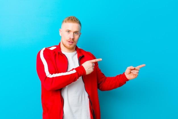 Jeune homme blond portant des vêtements de sport se sentant choqué et surpris, montrant l'espace de copie sur le côté avec un regard étonné et bouche bée