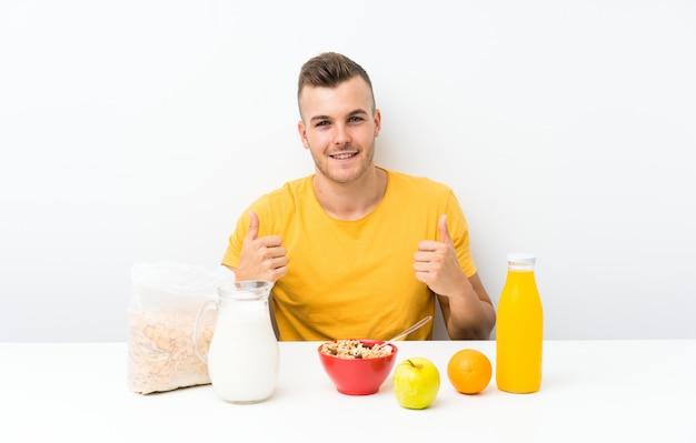 Jeune homme blond prenant son petit déjeuner donnant un geste du pouce levé