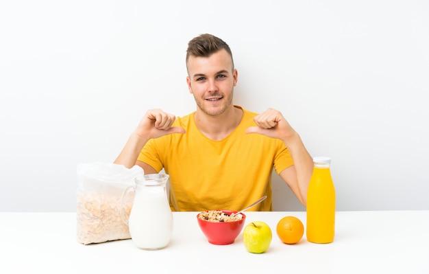 Jeune homme blond prenant son petit déjeuner fier et satisfait