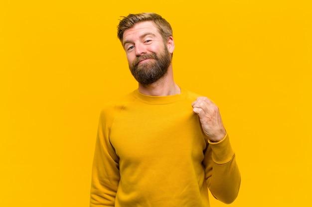 Jeune homme blond à la recherche d'arrogant, de succès, de positif et de fierté, se pointant contre le mur orange