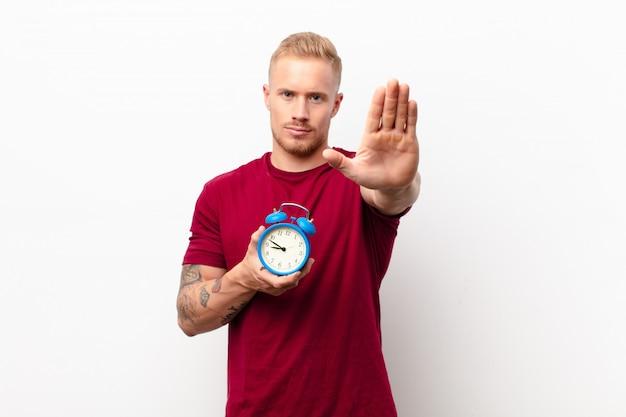 Jeune homme blond à la recherche de sérieux, sévère, mécontent et en colère montrant la paume ouverte faisant un geste d'arrêt sur un mur blanc tenant un réveil