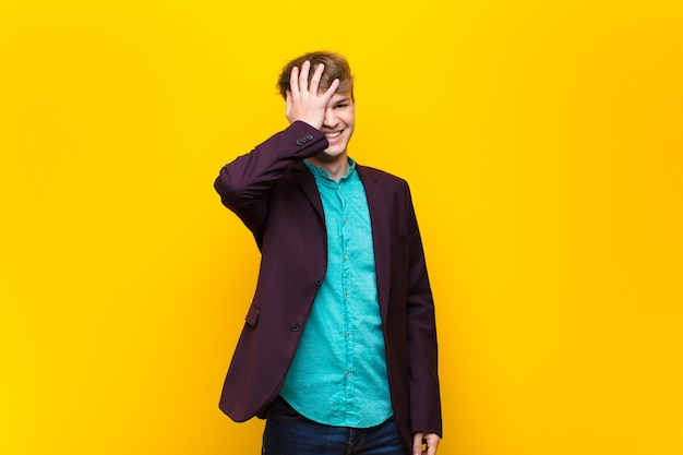 Jeune homme blond riant et giflant le front comme dire «oh! j'ai oublié ou c'était une erreur stupide isolée contre un mur plat