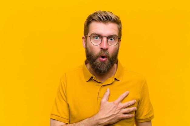 Jeune homme blond se sentant choqué et surpris, souriant, prenant la main à coeur, heureux d'être celui ou montrant sa gratitude contre le mur orange