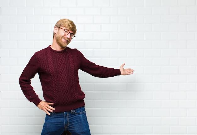 Jeune homme blond se sentant heureux et gai, souriant et vous accueillant, vous invitant avec un mur amical de carreaux vintage agaist
