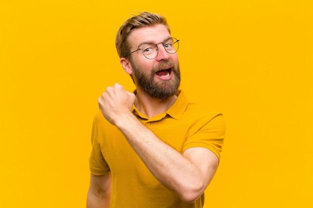Jeune homme blond se sentant heureux, positif et couronné de succès, motivé devant un défi ou célébrant de bons résultats contre le mur orange