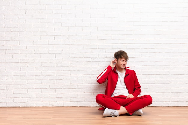 Jeune homme blond se sentant stressé, frustré et fatigué, se frottant le cou douloureux, avec un regard inquiet et troublé assis sur le sol