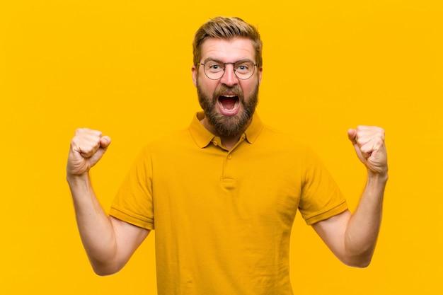 Jeune homme blond se sentir heureux, surpris et fier, crier et célébrer son succès avec un grand sourire