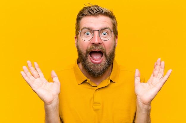 Jeune homme blond semblant heureux et excité, choqué par une surprise inattendue avec les deux mains ouvertes à côté du visage contre orange