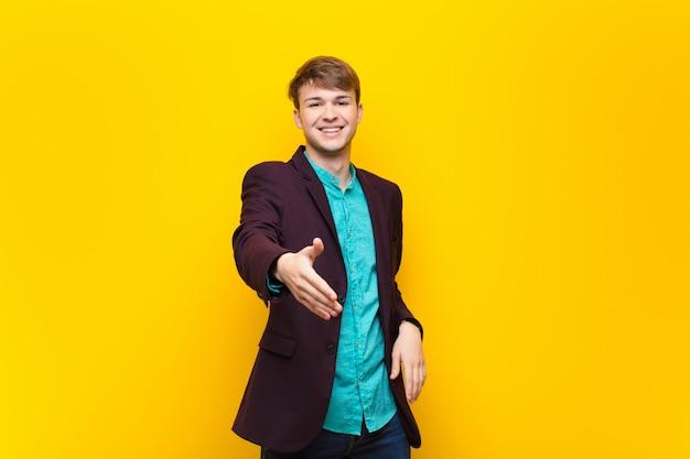Jeune homme blond souriant, l'air heureux, confiant et sympathique, offrant une poignée de main pour conclure un accord, coopérant sur le mur