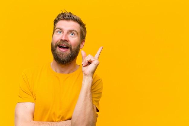 Jeune homme blond souriant avec bonheur et regardant de côté, se demandant, pensant avoir une idée mur orange