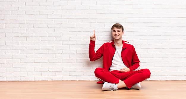 Jeune homme blond souriant joyeusement et joyeusement, pointant vers le haut avec une main pour copier l'espace assis sur le sol