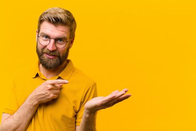 Jeune homme blond souriant joyeusement et pointant pour copier l'espace sur la paume sur le côté, montrant ou annonçant un objet contre le mur orange