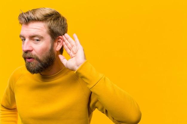 Jeune homme blond souriant regardant curieusement sur le côté en essayant d'écouter des commérages ou d'entendre un secret