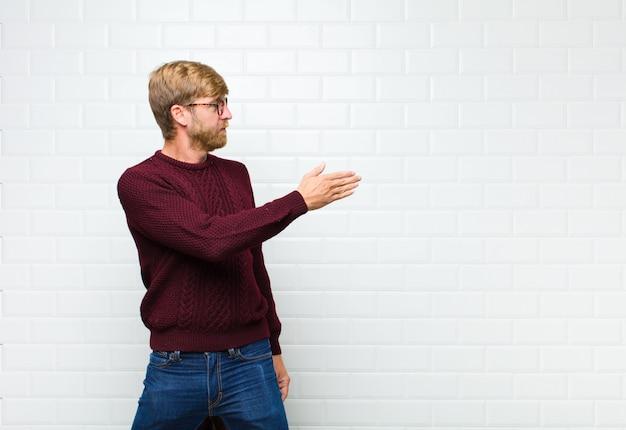 Jeune homme blond souriant, vous saluant et offrant une poignée de main pour conclure une affaire réussie, le concept de coopération agaist mur de carreaux vintage