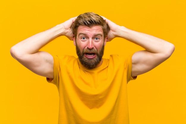 Jeune homme blond stressé, inquiet, anxieux ou effrayé, les mains sur la tête, paniqué par erreur sur le mur orange