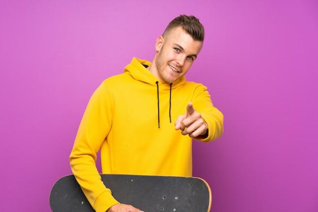 Jeune homme blond tenant un skate pointe le doigt vers vous avec une expression confiante