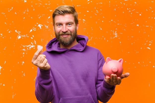 Jeune homme blond avec une tirelire portant un sweat à capuche violet