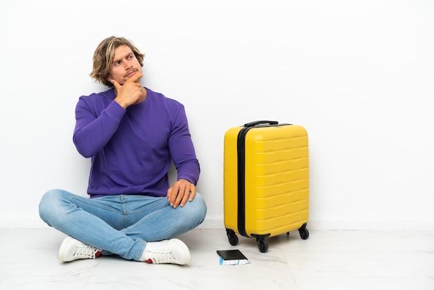 Jeune homme blond avec valise assis sur le sol ayant des doutes et avec l'expression du visage confus