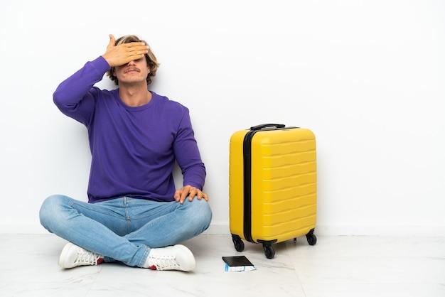 Jeune homme blond avec valise assis sur le sol couvrant les yeux par les mains. je ne veux pas voir quelque chose