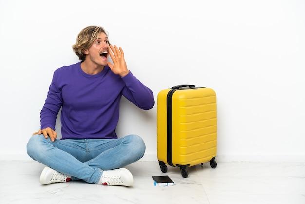 Jeune homme blond avec valise assis sur le sol en criant avec la bouche grande ouverte sur le côté