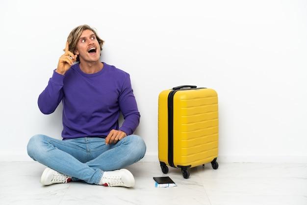 Jeune homme blond avec valise assis sur le sol dans l'intention