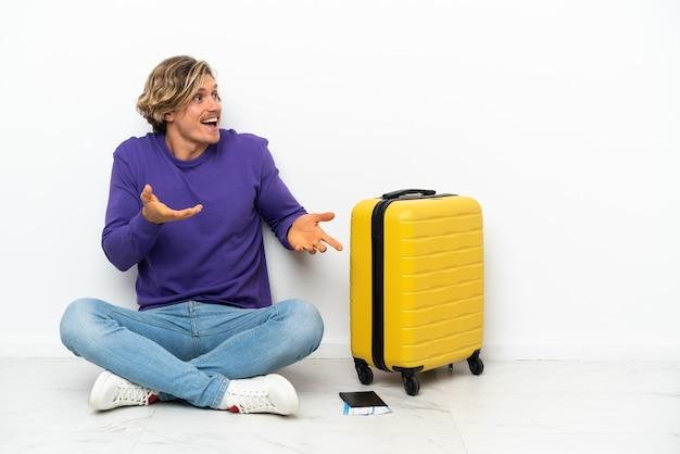 Jeune homme blond avec valise assis sur le sol avec une expression faciale surprise