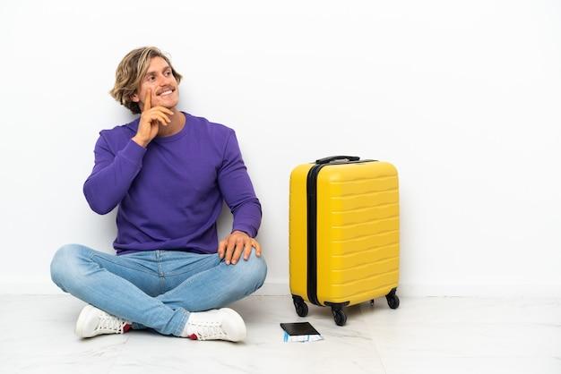 Jeune homme blond avec valise assis sur le sol en pensant à une idée tout en levant les yeux
