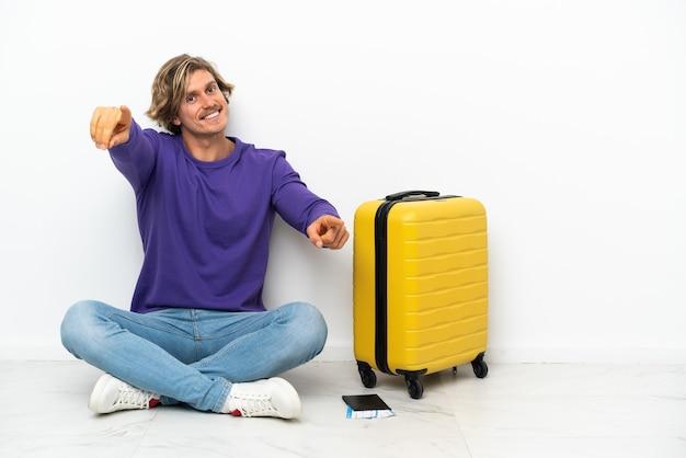 Jeune homme blond avec valise assis sur le sol pointe le doigt sur vous en souriant