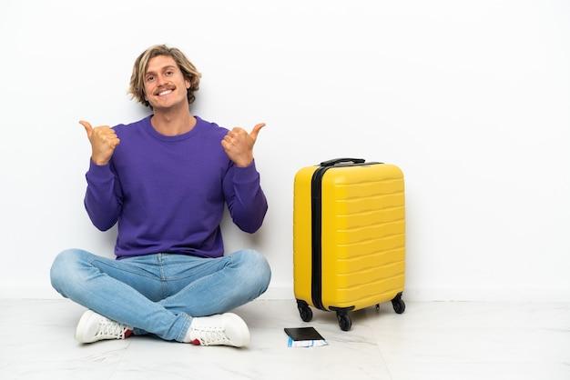 Jeune homme blond avec valise assis sur le sol avec le pouce en l'air et souriant