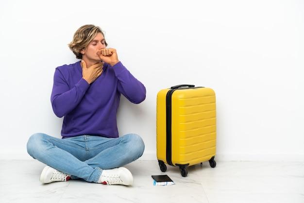 Jeune homme blond avec valise assis sur le sol souffre de toux et se sent mal