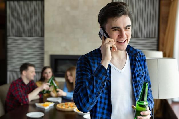 Jeune homme boit de la bière à partir d'une bouteille, parle au téléphone et regarde par la fenêtre d'un café