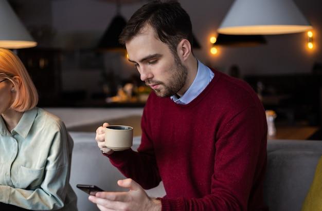 Un jeune homme boit du thé et regarde dans le smartphone