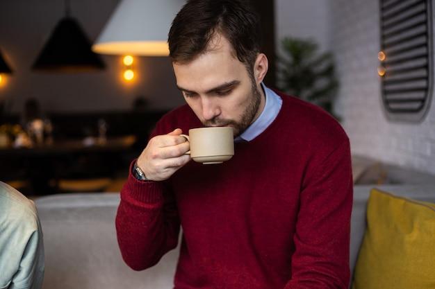Un jeune homme boit du thé