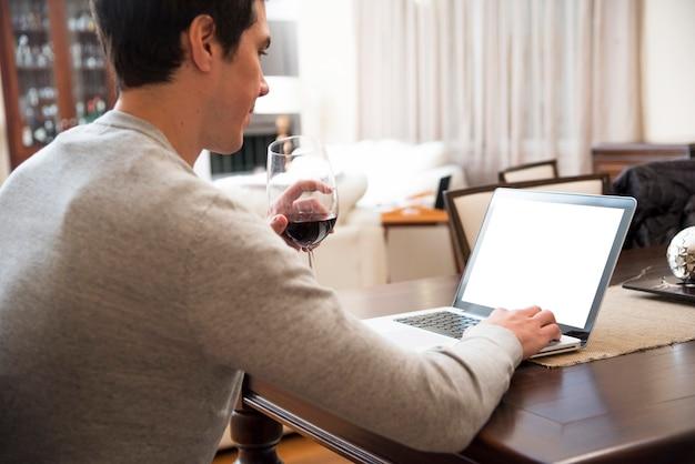 Jeune homme boit du vin tout en utilisant une tablette numérique à la maison