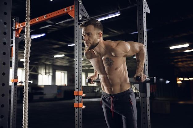 Jeune homme en bonne santé, athlète faisant des exercices, des tractions dans la salle de gym. modèle masculin célibataire pratiquant dur et entraînant le haut du corps. concept de mode de vie sain, sport, fitness, musculation, bien-être.