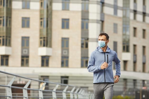 Jeune homme en bonne santé en masque de protection jogging seul dans la ville