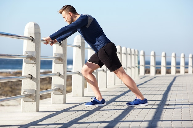 Un jeune homme en bonne santé s'étire dehors pour faire de l'exercice