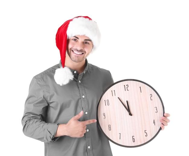 Jeune homme en bonnet de noel avec horloge sur fond blanc. notion de compte à rebours de noël