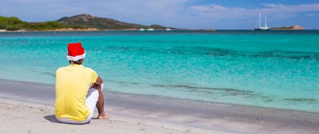Jeune homme en bonnet de noel pendant les vacances à la plage