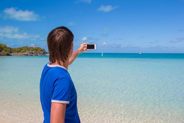 Jeune homme en bonnet de noel avec téléphone sur la plage des caraïbes tropicale