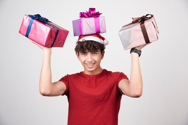 Jeune homme en bonnet de noel tenant un tas de cadeaux.